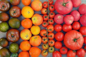 Different varieties of tomatoes on wooden background. Top view.